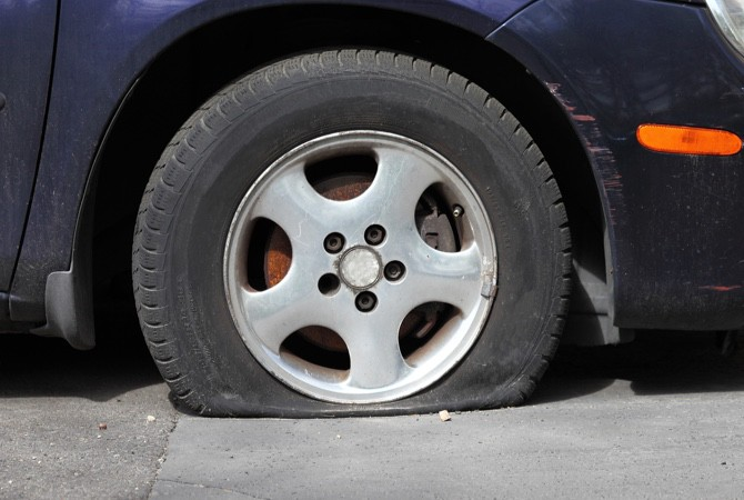 A close up of a flat tire on a car