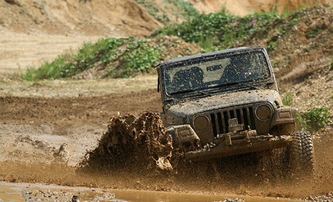 A Jeep driving through a large mud pit