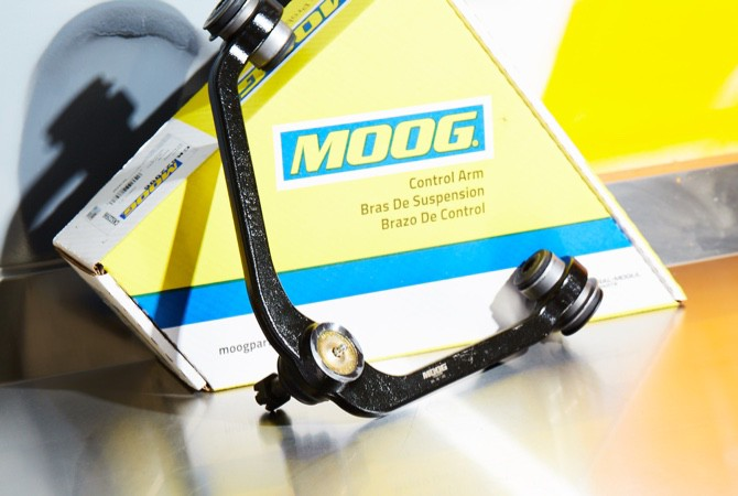 A MOOG control arm being presented infront of a MOOG control arm box