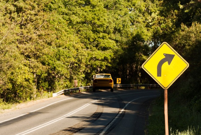 A yellow car, driving through a wooded area, misses a right turn sign and swerves off the road due to steering and suspension parts failure.
